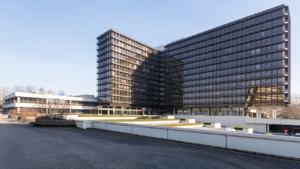 weite Aufnahme eines grau-schwarzen, mehrstöckigen Bürogebäudes mit mehreren Flügeln