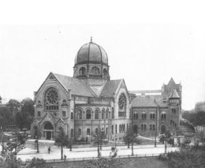schwarz-weiß Foto einer Synagoge mit Kuppeldach in der Mitte und großen runden Fenstern an zwei Giebeln.
